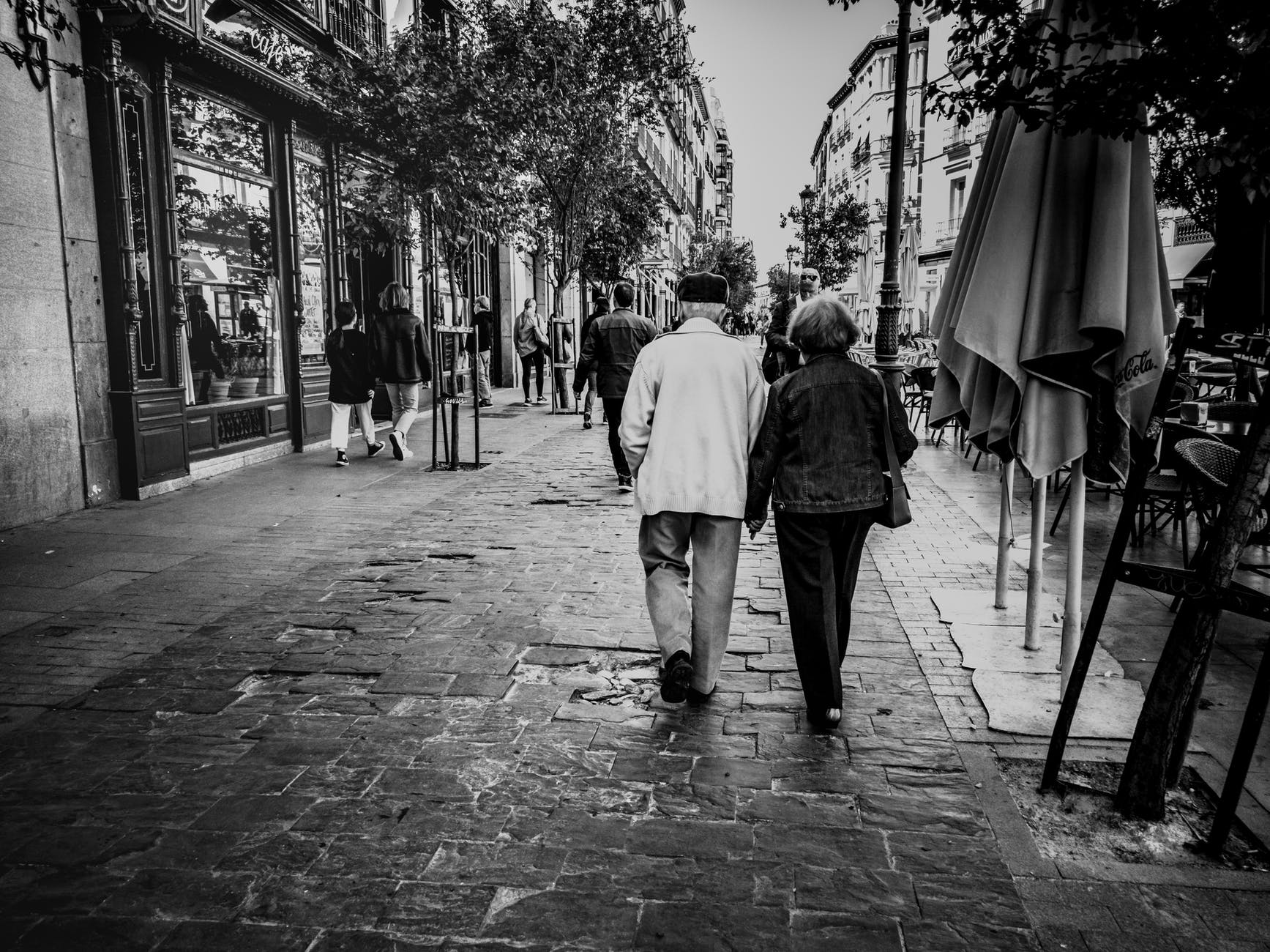 grayscale photography man and woman walking
